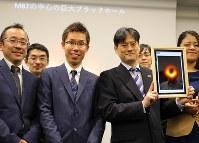 ブラックホールの撮影に世界初で成功し、画像を手にポーズを取る本間希樹国立天文台教授(中央右)と秦和弘国立天文台助教授(中央左)=東京都千代田区で2019年4月10日午後11時52分、宮武祐希撮影