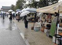 雨の中幕を開けた「平安蚤の市」=京都市左京区の岡崎公園で2019年4月10日11時19分、菅沼舞撮影