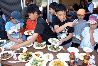 野草料理を食べる子どもたち=高知県四万十市津蔵渕の「四万十ふれーばー」で