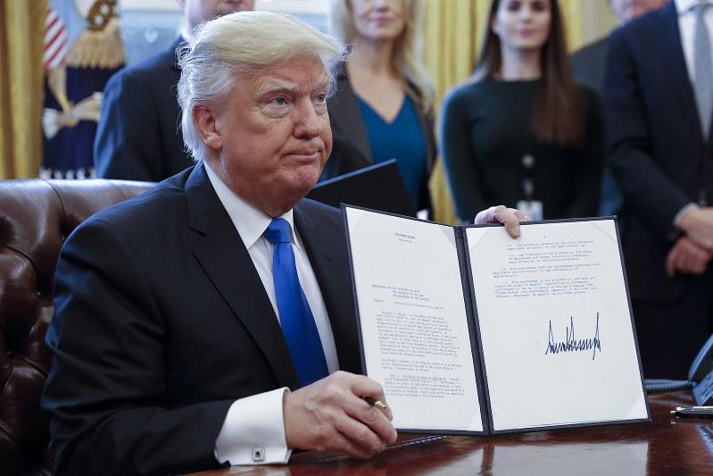 米国のエネルギー戦略は安全保障と表裏一体だ(2017年1月、石油パイプライン建設の大統領令にサインしたトランプ大統領)(Bloomberg)