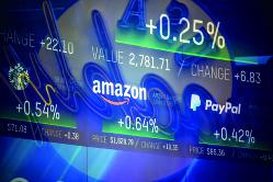 史上最高値まであと一息(ナスダック市場の値動きを示すニューヨークの株価ボード)(Bloomberg)