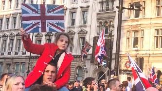 「(EU離脱の)延期は裏切りだ」などと書かれたプラカードを手に議会前の道路をデモ行進する離脱派市民ら=2019年3月29日、三沢耕平撮影