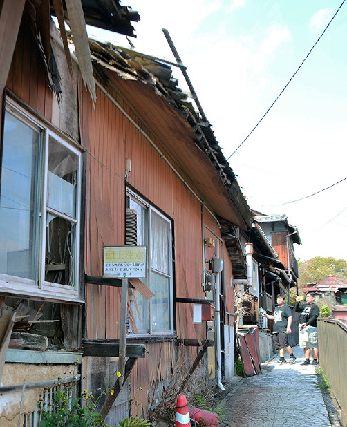 屋根が壊れ、窓ガラスが割れた空き家を撮影する観光客。「頭上注意」の看板が設置されている=広島県尾道市で、渕脇直樹撮影