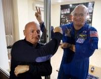 4月11日、米国で生まれた一卵性双生児の一方が飛行士として宇宙空間を経験していた間に、生物的変化が生じたものの、地球に戻ってからはほぼ通常の状態に戻ったことが、11日公表された研究結果で分かった。写真は双子のスコット・ケリー氏(右)とマーク・ケリー氏。2015年3月26日、カザフスタンのバイコヌール宇宙基地で撮影(2019年 ロイター/)
