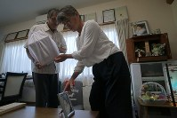 熊本地震で犠牲になった河添由実さんの遺骨を墓に納骨するため、仏壇から運び出す(左から)父敏明さんと母登志子さん=熊本県益城町で2018年8月19日、和田大典撮影