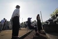 熊本地震で犠牲になった河添由実さんの遺骨を墓に納骨し手をあわせる親族たち=熊本県益城町で2018年8月19日、和田大典撮影