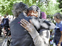 A white woman, foreground, hugs a Muslim woman, after a shooting attack at a mosque in Christchurch, in New Zealand's South Island, on March 19, 2019. (Mainichi/Shizuya Fukuoka)