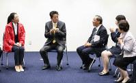 福島県大熊町役場の新庁舎内で、地元産のお米で作ったおにぎりを食べる安倍晋三首相(左から2人目)=2019年4月14日午後0時39分(代表撮影)