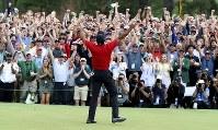 男子ゴルフのメジャー第1戦、マスターズ・トーナメントで14年ぶり5度目の優勝を果たし、両手を上げて喜ぶタイガー・ウッズ=AP