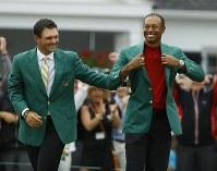 14年ぶりの優勝を決め、グリーンジャケットを着て笑顔を見せるタイガー・ウッズ=AP
