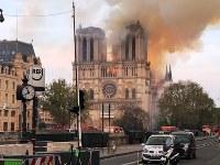 ノートルダム大聖堂から200メートル離れたサンミシェル橋にも火の粉が舞った=パリで15日、賀有勇撮影