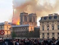 ノートルダム大聖堂にある尖塔は激しく燃えた後に崩れ落ちた=パリで15日、賀有勇撮影