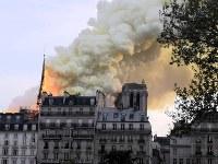 ノートルダム大聖堂から立ち上る白煙=パリで15日、賀有勇撮影