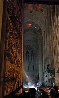 炎上する屋根から火の粉が舞い落ち、白煙が上がるノートルダム大聖堂の内部=パリで2019年4月15日、AP