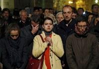 ノートルダム大聖堂が炎上し、街頭で祈る人たち=パリで2019年4月15日、AP