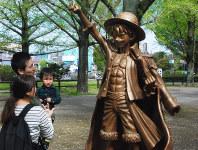 熊本県庁前に設置されているルフィ像を観賞する親子連れ=熊本市中央区で2019年4月17日午前9時21分、中里顕撮影