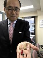 耳穴型や耳かけ型などさまざまな補聴器を示す日本補聴器工業会の木村修造さん=梅田啓祐撮影