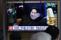 People watch a TV news program reporting about North Korea's test-firing of a
