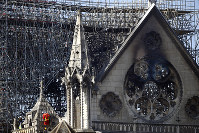 A fire fighter makes his way on a balcony of Notre Dame Cathedral on April 17, 2019, in Paris. (AP Photo/Francois Mori)