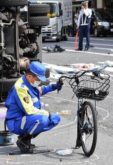多重事故で引きちぎられた自転車の前部を調べる警視庁の捜査員ら。後方にあるのは引きちぎられた自転車の後部=東京都豊島区で2019年4月19日午後2時7分、宮間俊樹撮影