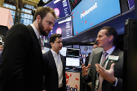 Pinterest co-founder & CEO Ben Silbermann, center, and fellow co-founder and chief product officer Evan Sharp, left, meet with specialist Glenn Carell on the New York Stock Exchange trading floor, on April 18, 2019, before the company's IPO. (AP Photo/Richard Drew)