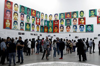 People stand under portraits of 43 college students who went missing in 2014 in an apparent massacre, by Chinese concept artist and government critic Ai Weiwei at the Contemporary Art University Museum (MUAC) in Mexico City, Mexico, on April 13, 2019. (AP Photo/Claudio Cruz)