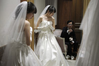In this April 11, 2019, photo, Kenzo Watanabe, right, looks at his fiancee Chiharu Yanagihara trying on a wedding dress at a Japanese wedding company in Tokyo. (AP Photo/Eugene Hoshiko)