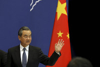 Chinese Foreign Minister Wang Yi waves as he leaves after a press conference on the upcoming Road and Belt Forum in Beijing, on April 19, 2019. (AP Photo/Ng Han Guan)