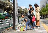 歩行者らがはねられた現場に花を供え、亡くなった母子を悼む親子連れ=東京都豊島区で2019年4月20日午前8時50分、渡部直樹撮影