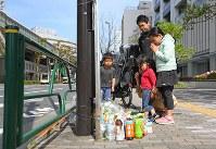 歩行者らがはねられた現場で手を合わせ、亡くなった母子を悼む親子連れ=東京都豊島区で2019年4月20日午前8時50分、渡部直樹撮影