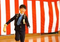 入学式後、筋電義手を手に持ちながら走り回り笑顔を見せる佐藤亮介くん=埼玉県で2019年4月9日、宮武祐希撮影