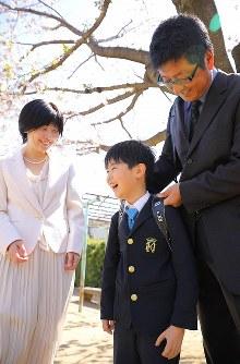 入学式前、笑顔を見せる佐藤亮介くん(中央)。左は母の秀美さん、右は父の泰三さん=埼玉県で2019年4月9日、宮武祐希撮影