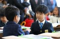 クラスが決まり、隣の席になった友達と握手する佐藤亮介くん(右)=埼玉県で2019年4月9日、宮武祐希撮影