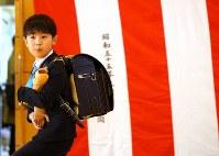 入学式後、筋電義手を手に歩く佐藤亮介くん=埼玉県で2019年4月9日、宮武祐希撮影