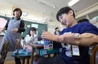 小学校入学後の初めての給食で、筋電義手を使って牛乳パックをつぶすして見せる佐藤亮介くん(右)=埼玉県で2019年4月11日、宮武祐希撮影