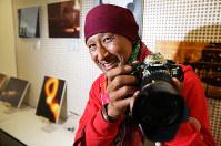 入院中、自身で撮影した写真の前でポーズをとる高橋貴久男さん=兵庫県芦屋市で2019年4月17日午後2時42分、小出洋平撮影