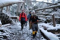 明け方、雪の残る山道を下る中島浩彰さん(手前)ら。2018年の台風の影響で道をふさぐ倒木も=京都市左京区で2019年2月12日、花澤茂人撮影