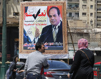 People walk past a banner supporting proposed amendments to the Egyptian constitution with a poster of Egyptian President Abdel-Fattah el-Sissi in Cairo, Egypt, on April 16, 2019. (AP Photo/Amr Nabil)