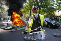 A man bangs a drum in front of a fire on the street during a yellow vest demonstration in Paris, Saturday, April 20, 2019. (AP Photo/Michel Euler)