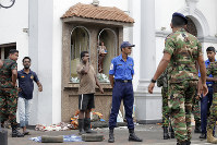 People gather outside St. Anthony's Shrine after a bomb went off in Colombo, Sri Lanka, Sunday, April 21, 2019. (AP Photo/Eranga Jayawardena)