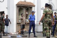People gather outside St. Anthony's Shrine after a bomb went off in Colombo, Sri Lanka, Sunday, April 21, 2019. (AP Photo/Eranga Jayawardena)