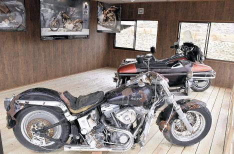 津波で被災したハーレーダビッドソン社製大型バイク2台。後ろは約6500キロ離れたカナダ西部に流れ着いたハーレーの写真=宮城県山元町で2019年4月21日、滝沢一誠撮影