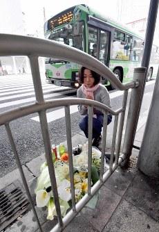 神戸市営バスの事故があった現場に花を供え、手を合わせる会社員の女性。仕事で通ることがあった横断歩道での事故を知り、慰霊に来たという=神戸市中央区で2019年4月22日午前8時20分、平川義之撮影