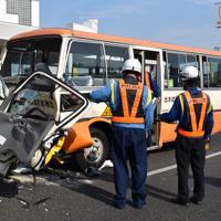事故現場で巻き込まれたこども園バスなどを調べる警察官ら=熊本市中央区で2019年4月22日午後4時9分、城島勇人撮影