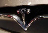 This Oct. 3, 2018 file photo shows a Tesla emblem at the Auto show in Paris. (AP Photo/Christophe Ena)