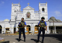 Sri Lankan soldiers stand guard in front of the St. Anthony's Shrine a day after the series of blasts, in Colombo, Sri Lanka, on April 22, 2019. (AP Photo/Eranga Jayawardena)