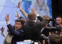 Ukrainian comedian and presidential candidate Volodymyr Zelenskiy, left, makes the victory sign after seeing the exit polls for the second round of presidential elections in Kiev, Ukraine, on April 21, 2019. (AP Photo/Vadim Ghirda)