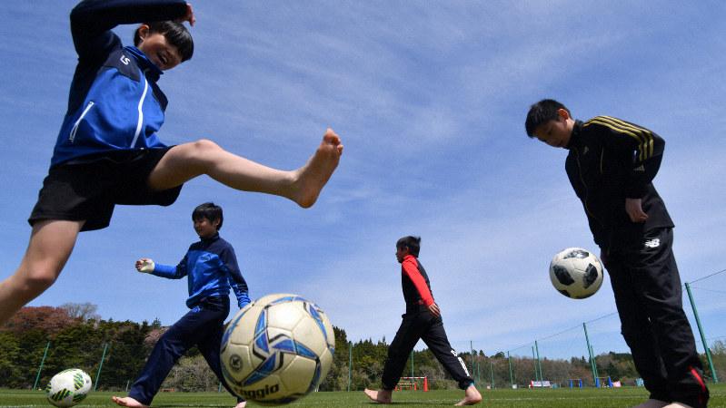 全面再開したJヴィレッジの天然芝グラウンドでサッカーを楽しむ子どもたち=福島県楢葉町で2019年4月20日、宮間俊樹撮影