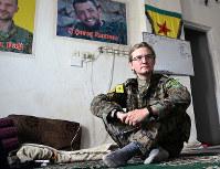 米国人義勇兵のハキ。部屋の壁には戦闘で死んだ仲間の写真が並ぶ=シリア・ハサカ近郊で2018年10月、玉本英子さん撮影
