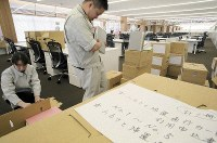 Staff unpack boxes filled with documents relating to the nuclear evacuation at the new municipal government building in Okuma, Fukushima Prefecture, on April 22, 2019. (Mainichi/Daisuke Wada)